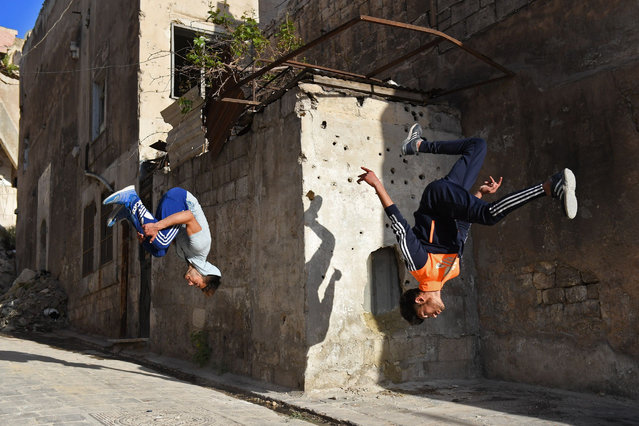 Syrian youths practice parkour in Aleppo, northern Syria, on April 7, 2018. The government retook full control of Aleppo from rebel- fighters in December 2016. (Photo by George Ourfalian/AFP Photo)