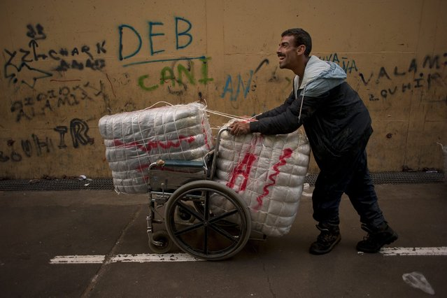 Hassan Ibrahim, a disabled man, uses his wheelchair to transport goods across El Tarajal separating Morocco and Spain's North African enclave of Ceuta, in Ceuta on December 4, 2014. (Photo by Jorge Guerrero/AFP Photo)
