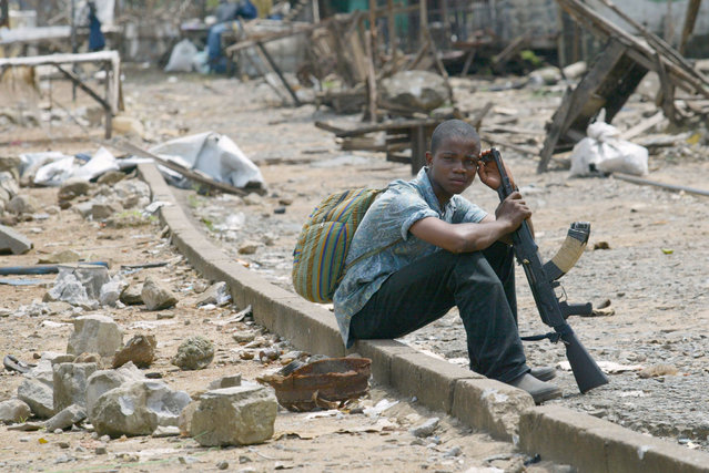 A young rebel of Liberians United for Reconciliation and Democracy (LURD) waits at the New Bridge in Monrovia August 9, 2003. (Photo by Juda Ngwenya/Reuters)