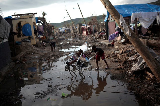 Two children play with a wheelchair in a street after Hurricane Matthew in Damassins, Haiti, October 22, 2016. (Photo by Andres Martinez Casares/Reuters)