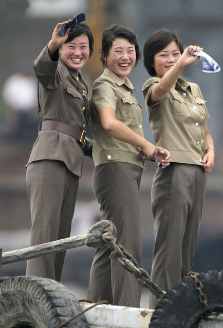 Female North Korean soldiers wave to a Chinese boat for tourists on the banks of Yalu River near the North Korean town of Sinuiju July 27, 2010. (Photo by Jacky Chen/Reuters)