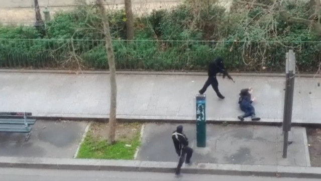 Gunmen shoot a wounded police officer (R) on the ground at point-blank range, outside the offices of French satirical newspaper Charlie Hebdo in Paris, in this still image taken from amateur video shot on January 7, 2015, and obtained by Reuters. Hooded gunmen stormed the Paris offices of the weekly satirical magazine known for lampooning radical Islam, killing at least 12 people. (Photo by Reuters/Handout via Reuters TV)
