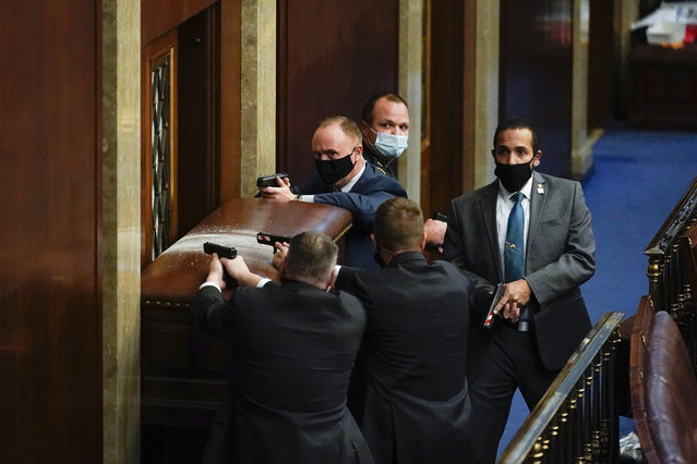 U.S. Capitol Police with guns drawn stand near a barricaded door as protesters try to break into the House Chamber at the U.S. Capitol on Wednesday, January 6, 2021, in Washington. (Photo by Andrew Harnik/AP Photo)