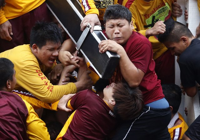 Devotees grimace as they try to hold the Black Nazarene, which is atop a carriage, at the start of an annual procession in Manila, January 9, 2015. More than a million barefoot devotees joined the parade ahead of Pope Francis' visit to the Philippines next week. (Photo by Erik De Castro/Reuters)