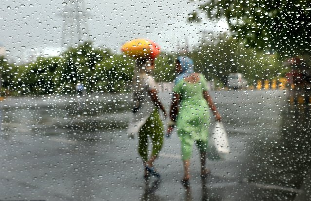 Indian women are seen through a glass with rain drops after a sudden rainfall on outskirts of New Delhi, India, 25 June 2020. According to India Meteorological Department (IMD), monsoon rain will hit Delhi and to give the respite soon from the summer heat. (Photo by Harish Tyagi/EPA/EFE)
