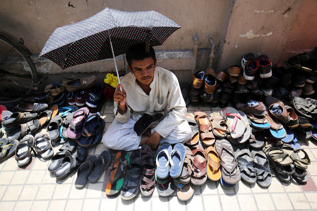 A man uses an umbrella to shelter himself from the sun as he takes care of shoes outside a mosque during the second Friday prayers of the holy fasting month of Ramadan, in Ahmedabad, India, May 25, 2018. (Photo by Amit Dave/Reuters)