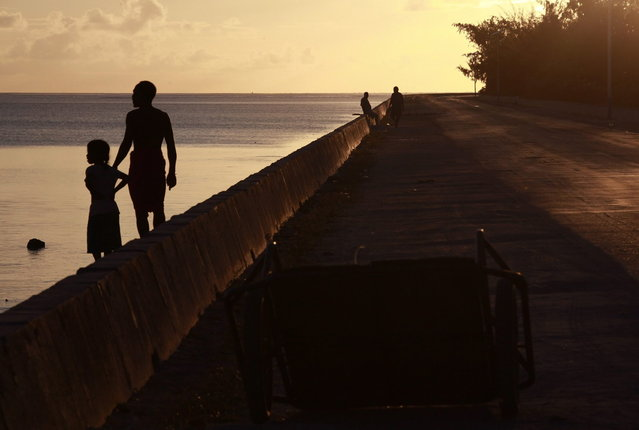 Locals stand on a causeway, which allows travel between the atolls of South Tarawa, near the town of Bairiki in the central Pacific island nation of Kiribati May 25, 2013. (Photo by David Gray/Reuters)