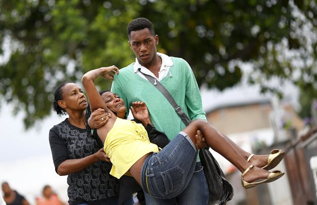 Relatives of Wilton Esteves Domingos, one of five youths killed after being shot by police officers in Costa Barros neighborhood, react after his burial in Rio de Janeiro, Brazil, November 30, 2015. Five youths aged between 16 and 25 years old were killed inside a car when policemen fired about fifty bullets against them when they were driving around, near the Lagartixa slum, local media reported. (Photo by Ricardo Moraes/Reuters)