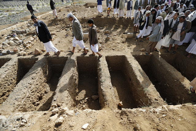 People walk past graves which were dug up for soldiers killed in the Wadi Hadramout region in northeastern Yemen, at a military cemetery in Sanaa August 10, 2014. (Photo by Khaled Abdullah/Reuters)