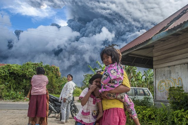 Indonesia's Mount Sinabung erupts, sending a column of volcanic materials as high as 16,000 feet into the sky on August 10, 2020. The volcano, one of two currently erupting in Indonesia, was dormant for four centuries before exploding in 2010, killing two people. Another eruption in 2014 killed 16 people, while seven died in a 2016 eruption. (Photo by Sutanta Aditya/Abaca/Sipa USA via AP Images)