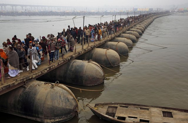 "Indian Hindu devotees walk across a pontoon bridge to arrive at the Sangam, the confluence of the Ganges, Yamuna, and the mythical Saraswati on ""Mauni Amavasya"" or new moon day, the third and the most auspicious date of bathing during the annual month long Hindu religious fair ""Magh Mela"" in Allahabad, India,Tuesday, January 20, 2015. (Photo by Rajesh Kumar Singh/AP Photo)"