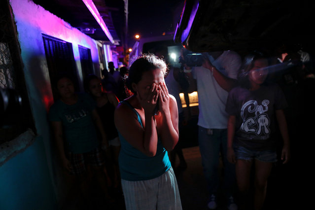 """A relative cries near the scene where a 17 year old girl and a 21 year old man were killed by unknown motorcycle-riding gunmen in an alley in Manila, Philippines early October 26, 2016. According to the police, a sign on a cardboard reading """"Tulak ka, hayop ka"""", which translates to """"You are a (drug) pusher, you are an animal"""" was found with the the body of the killed man. (Photo by Damir Sagolj/Reuters)"""