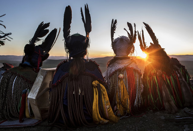 Mongolian Shamans or Buu, sit together as they take part in a sun ritual ceremony to mark the period of the Summer Solstice in the grasslands on June 22, 2018 outside Ulaanbaatar, Mongolia. Banned for 70 years under Communist rule, shamanism has seen a resurgence in Mongolia since 1992, when the ancient practice became protected by the country's Constitution. Known as Tengrism, in which Shamans channel ancestral spirits, it is widely regarded as Mongolia's national religion and part of its indigenous identity. Shamans, it is believed, are chosen by their ancestral spirits to serve as a bridge to the living world; a conduit to provide healing, knowledge, and advice. Mongolia shamanism emerged from the grasslands thousands of years before Chinggis Khan founded the Mongol empire and has evolved with rituals in worship of nature and the eternal blue sky. Modern-day Shamans are more typically consulted for advice in business deals, illness, or personal difficulties. Shamans employ tools, including headdresses and mouth harps, to induce trances for the spirits to use their bodies and voices. While there are no official numbers, it is believed there are over 10,000 Shamans in Mongolia, and many have formed unions, organizations, and collectives. (Photo by Kevin Frayer/Getty Images)