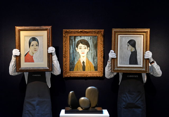 """Art handlers pose with """"Ann in a Red Jumper"""" (L) and """"Portrait of Ann"""" (R) with """"Head of a Boy"""" (C) all painted by LS Lowry, as preparations take place at Christie's ahead of a livestream auction of Modern British Art on March 1, in London, Britain, February 17, 2021. (Photo by Toby Melville/Reuters)"""