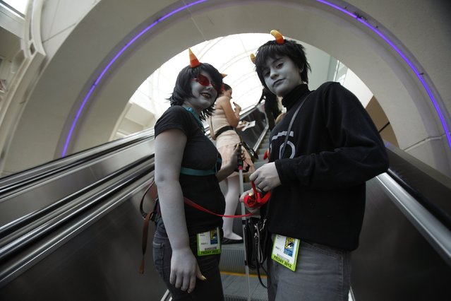 Attendees Delaney Oldenburg (L) and Sabrina Zaitz, who are wearing costumes inspired by the webcomic Homestuck, ride an escalator during Comic-Con international convention in San Diego, California July 13, 2012. (Photo by Mario Anzuoni/Reuters)