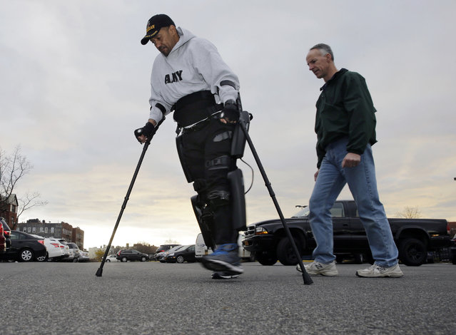 ReWalk Robotics service engineer Tom Coulter, right, looks on as paralyzed Army veteran Gene Laureano makes a turn while he walks using a ReWalk device Wednesday, December 16, 2015, in Bronx, N.Y. The Department of Veterans Affairs has agreed to pay for robotic legs that could allow scores of paralyzed veterans with spinal cord injuries to walk again. (Photo by Mel Evans/AP Photo)