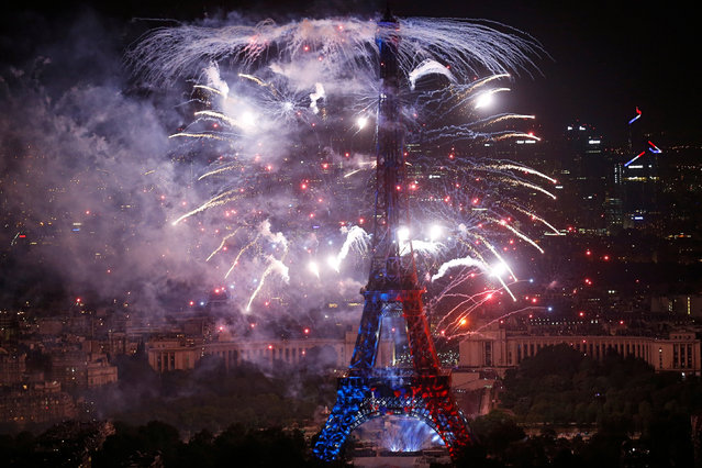 Fireworks explode near the Eiffel Tower, in a picture taken from the Montparnasse Tower Observation Deck, at the end of Bastille Day events in Paris, France, July 14, 2018. (Photo by Pascal Rossignol/Reuters)