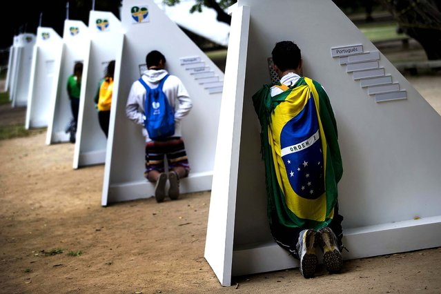 Catholics kneel at portable confessionals set up in Quinta da Boa Vista park during World Youth Day events in Rio de Janeiro, on July 23, 2013. The pope is in Brazil on a seven-day visit meant to fan the fervor of the faithful around the globe. (Photo by Silvia Izquierdo/Associated Press)