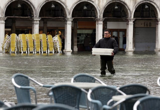 A man carries materials as he walks across the flooded St. Mark's Square during a period of seasonal high water and on the first day of carnival, in Venice February 1, 2015. (Photo by Stefano Rellandini/Reuters)
