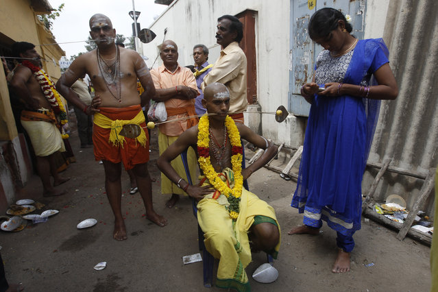 Hindu devotees, their cheeks pierced with metal rods, wait to participate in a religious procession during Thaipusam festival in Chennai, India, Tuesday, February 3, 2015. Thaipusam, celebrated in honor of Hindu god Lord Murugan, is an annual procession by Hindu devotees seeking blessings, fulfilling vows and offering thanks. (Photo by Arun Sankar K./AP Photo)