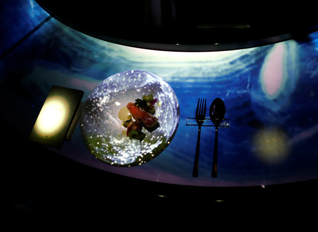 """The projection mapping is cast on a plate during its media preview at """"TREE BY NAKED, yoyogi park"""" restaurant in Tokyo, Japan on July 19, 2018. (Photo by Kim Kyung-Hoon/Reuters)"""