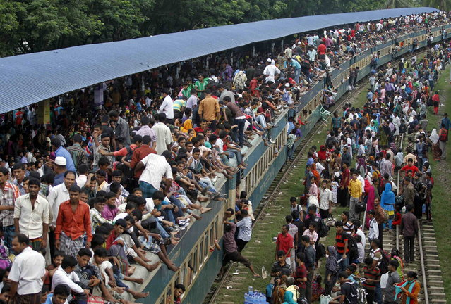 Passengers climb to board an overcrowded train at a railway station in Dhaka August 8, 2013. Millions of residents in Dhaka are travelling home from the capital city to celebrate the Muslim Eid al-Fitr holiday, which marks the end of the Muslim holy fasting month of Ramadan. (Photo by Andrew Biraj/Reuters)