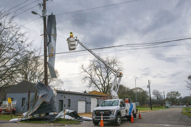 A utility worker looks to repair lines with the roof of Kelley Electric draped on the lines after downtown Moundville was hit by severe weather, Wednesday, March 17, 2021, in Moundville, Ala. Possible tornadoes knocked down trees, toppled power lines and damaged homes in rural Chilton County and the Alabama communities of Burnsville and Moundville, where power was out and trees blocked a main highway. (Photo by Vasha Hunt/AP Photo)
