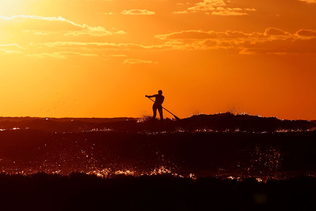 An Israeli youth rides a stand up paddle board at sunset on the shore of the coastal city of Netanya, north of Tel Aviv, on January 21, 2021, during a nationwide lockdown after a spike in COVID-19 cases. (Photo by Jack Guez/AFP Photo)