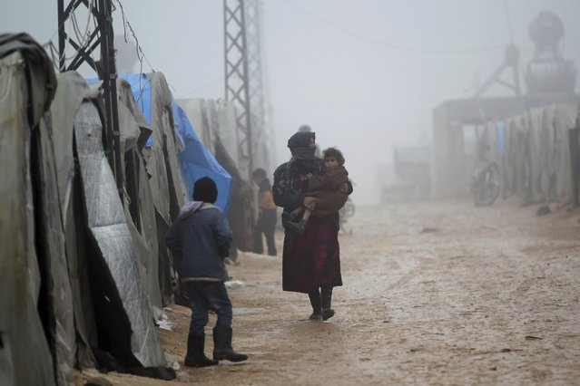A woman holds her daughter as she walks outside tents housing internally displaced people, during cold weather in Jerjnaz camp, in Idlib province, Syria, January 5, 2016. (Photo by Khalil Ashawi/Reuters)