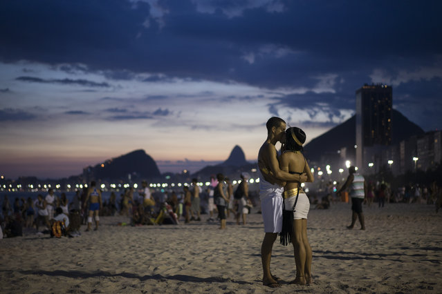 A couple kiss after the 'Bloco Virtual' carnival parade on the sands of Leme Beach, where the parade took place, in Rio de Janeiro, Brazil, Friday, February 13, 2015. The five days of over-the-top parades and raucous, alcohol-soaked street parties that make up Rio de Janeiro's world-famous Carnival celebrations kicked off Friday. (Photo by Felipe Dana/AP Photo)