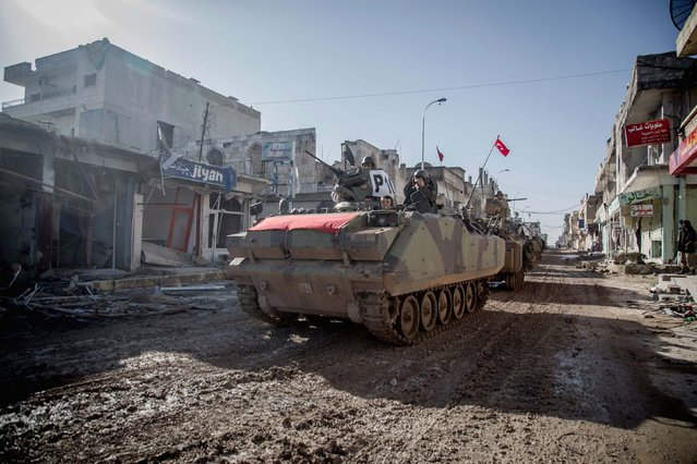 """Turkish tanks are pictured in the northern Syrian town of Kobani as they return from a military operation inside Syria February 22, 2015. Turkish forces swept into Syria overnight to rescue about 40 soldiers who had been surrounded for months by Islamic State militants while guarding the tomb of a revered Turkish figure. The Syrian government described the operation as act of """"flagrant aggression"""" and said it would hold Ankara responsible for its repercussions. The action, which involved tanks, drones and reconnaissance planes as well as several hundred ground troops, was the first such incursion by Turkish troops into Syria since the start of the civil war there nearly four years ago. (Photo by Mursel Coban/Reuters/Depo Photos)"""