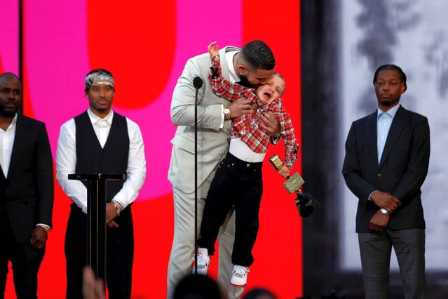 Canadian rapper Drake, accompanied by his son Adonis, accepts the award for Artist of the Decade at the 2021 Billboard Music Awards outside the Microsoft Theater in Los Angeles, California, U.S., May 23, 2021. (Photo by Mario Anzuoni/Reuters)
