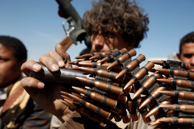 A pro-Houthi tribesman holds the barrel of a machine gun he carries during a gathering held to mobilize fighters for the battles against government forces, in Sanaa, Yemen November 24, 2016. (Photo by Khaled Abdullah/Reuters)