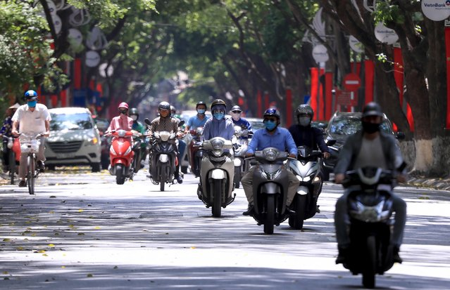 People ride motorcycles in Hanoi, Vietnam Monday, May 31, 2021. Vietnam plans to test all 9 million people in its largest city for the coronavirus and imposed more restrictions Monday to deal with a growing COVID-19 outbreak. (Photo by Hau Dinh/AP Photo)