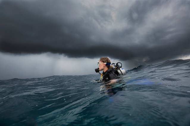 """Simon Dunn, runner-up, September winner. """"South Ari Atolls, Maldives. The photo shows my partner and dive buddy, Emma, surfacing after the last dive of the day to 1.5 metre swells and dark monsoon clouds. The image shows just how unforgiving the sea and weather changes can be in the Indian Ocean"""". MICK RYAN, JUDGE: This is active travel photography, with the photographer and subject in the thick of it. This beautiful portrait of a diver below a menacing sky stands out for its emotional and elemental beauty. It is a reminder that while we may play among nature, we are always dwarfed by its power. (Photo by Simon Dunn/The Guardian)"""