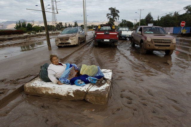 A woman rests on a mattress on a mud covered street after rains caused heavy flooding in Copiapo, Chile, Thursday, March 26, 2015. (Photo by Aton Chile/Marcelo Hernandez/AP Photo)