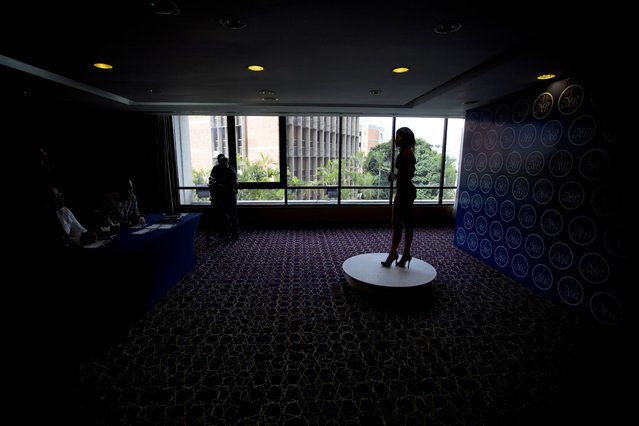 In this June 23, 2018 photo, a contestant wearing a swimsuit answers a question from a judge during an interview at a casting for Miss Our Beauty Venezuela Contest, at a hotel in Caracas, Venezuela. As the nation plummets into economic ruin, even more young women are holding fast to dreams of becoming beauty queens. (Photo by Fernando Llano/AP Photo)