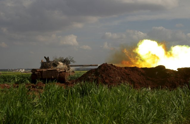 Rebel fighters from the Ahrar al-Sham Islamic Movement fire from a tank during what they said was an offensive to take the northwestern city of Idlib March 24, 2015. An alliance of Syrian Islamist rebels including al Qaeda's official wing said they had launched an offensive on Tuesday to take the northwestern city of Idlib, which is close to the main strategic highway linking Damascus to Aleppo. Picture taken March 24, 2015. (Photo by Khalil Ashawi/Reuters)