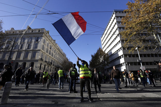 A demonstrator wearing a yellow vest waves the French flag during a march Saturday, December 8, 2018 in Marseille, southern France. The grassroots movement began as resistance against a rise in taxes for diesel and gasoline, but quickly expanded to encompass frustration at stagnant incomes and the growing cost of living. (Photo by Claude Paris/AP Photo)