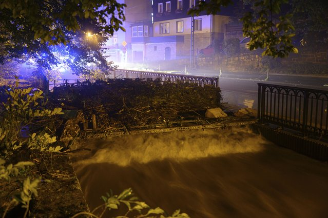 The Kirnitzsch river has washed up wood and debris on a bridge in Bad Schandau, Germany, Saturday, July 17, 2021. Days of heavy rain in Western Europe turned normally minor rivers and streets into raging torrents this week and caused the disastrous flooding that swept away cars, engulfed homes and trapped residents. (Photo by Robert Michael/dpa via AP Photo)