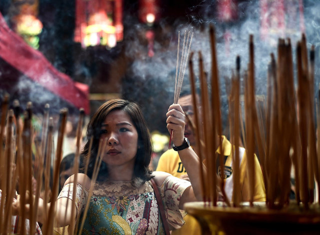 An ethnic Malaysian-Chinese devotee burns incense for good luck at the Guan Di Temple on the first day of the Lunar New Year in Kuala Lumpur's popular Chinatown area on February 8, 2016. Some 25 percent of Malaysia's 29 million people are ethnic Chinese and celebrate the Lunar New Year, this year marking the Year of the Monkey. (Photo by Manan Vatsyayana/AFP Photo)