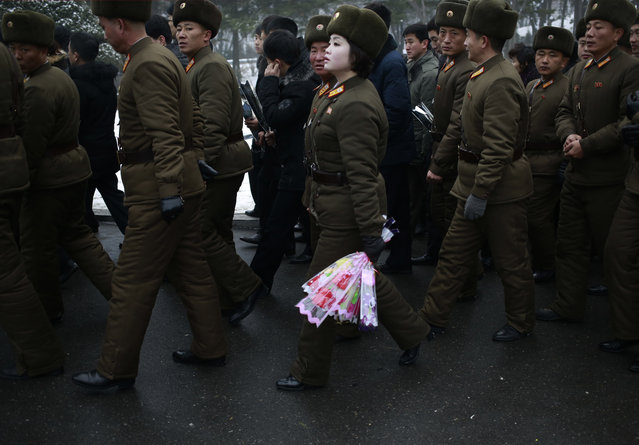 A member of North Korean military holds flowers to be laid at the bronze statues of the late leaders Kim Il Sung and Kim Jong Il at Mansu Hill Grand Monument in Pyongyang, North Korea, Monday, December 17, 2018. North Koreans are marking the seventh anniversary of the death of leader Kim Jong Il with visits to the statues and vows of loyalty to his son, Kim Jong Un. (Photo by Dita Alangkara/AP Photo)
