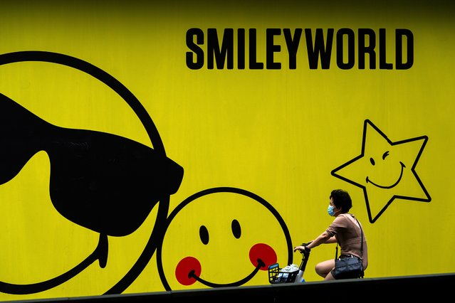 A woman wearing a face mask to help curb the spread of the coronavirus bicycles past a smiley faces billboard outside a shopping mall in Beijing, Monday, July 19, 2021. (Photo by Andy Wong/AP Photo)