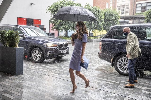"""Britain's Catherine, Duchess of Cambridge, shelters from the rain under an umbrella as she arrives at the London School of Economics to mark the launch of The Royal Foundation Centre for Early Childhood, where she took part in a roundtable discussion on the Centre's inaugural report, """"Big Change Starts Small"""" which was released today, in London on June 18, 2021. (Photo by Richard Pohle/Pool via AFP Photo)"""