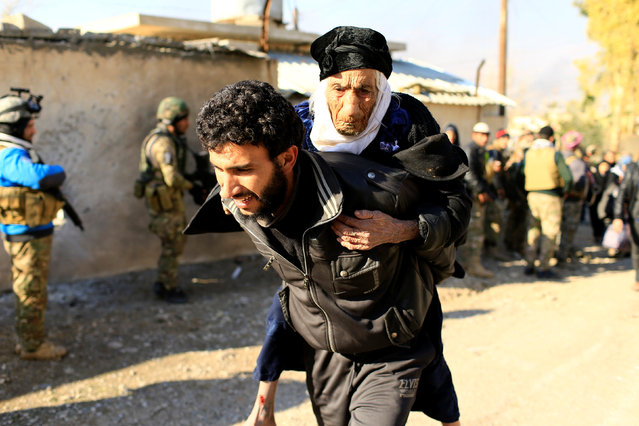 A displaced man, who fled the Islamic State stronghold of Mosul, carries a woman in the Mithaq district of eastern Mosul, Iraq, January 3, 2017. (Photo by Thaier Al-Sudani/Reuters)