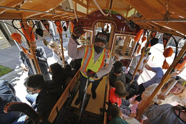 San Francisco cable car gripman Francis Givens rings the bell while on the Powell-Hyde line in San Francisco on Monday, August 2, 2021. San Francisco's iconic cable cars were chiming their bells and rolling again on the city's hills Monday after being sidelined for 16 months by the coronavirus pandemic. At Powell and Market, one of the cable car's stops, a line of people snaked around a cable car turntable waiting to ride a car to Ghirardelli Square or Fisherman's Wharf. (Photo by Jose Carlos Fajardo/Bay Area News Group via AP Photo)