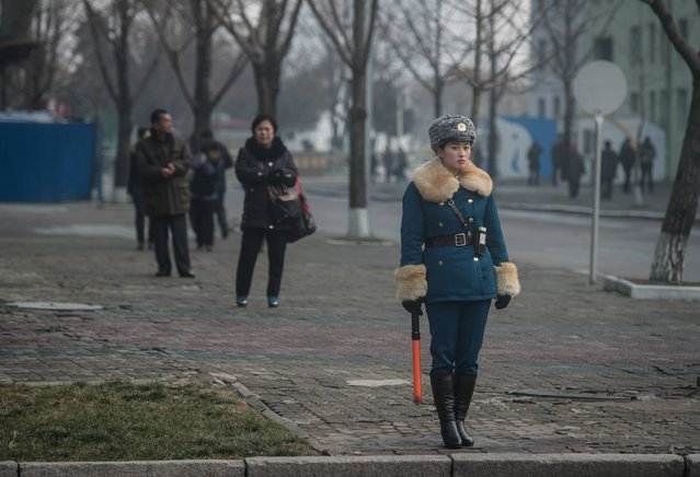 In a photo taken on November 27, 2016 a female traffic police officer directs traffic on a road in Pyongyang. Believed to be hand-picked for their looks, Pyongyang's female traffic police are a familiar sight at intersections around the capital, where traffic volumes have noticeably increased in recent years. (Photo by Ed Jones/AFP Photo)