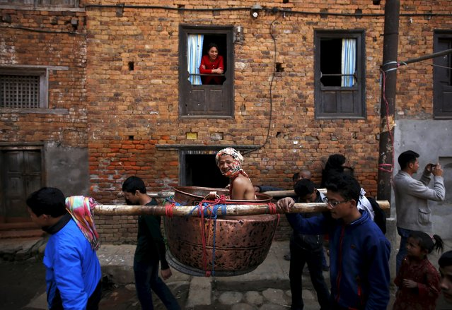 A devotee is carried around town in a vessel as part of rituals during the Swasthani Bratakatha festival at Thecho in Lalitpur, Nepal, February 19, 2016. During the month long festival, devotees recite one chapter of a Hindu tale daily from the 31-chapter sacred Swasthani Brata Katha book that is dedicated to God Madhavnarayan and Goddess Swasthani, alongside various other gods and goddess and the miraculous feats performed by them. (Photo by Navesh Chitrakar/Reuters)