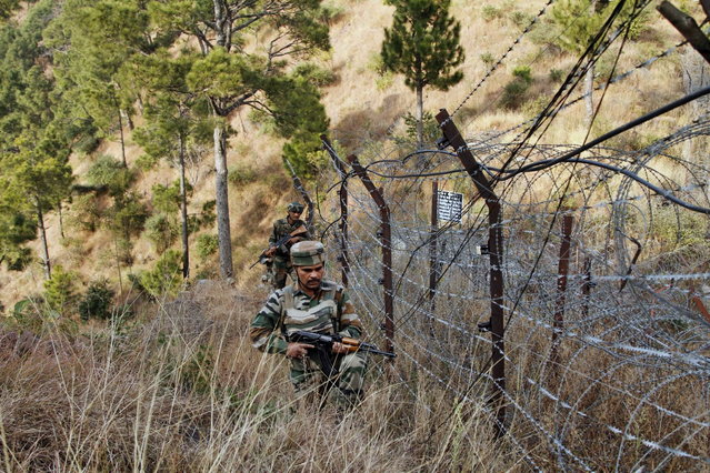 In this December 23, 2013 photo, Indian army soldiers patrol near one of their forward post at the Line of Control (LOC), that divides Kashmir between India and Pakistan, at Krishna Ghati (KG Sector) in Poonch, 290 kilometers (180 miles) from Jammu, India. (Photo by Channi Anand/AP Photo)