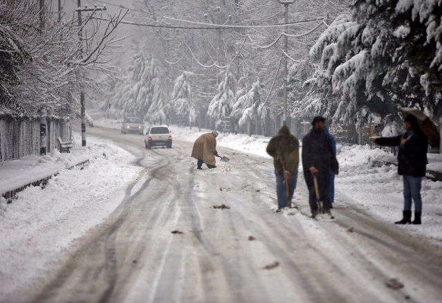 Men shovel snow to clear a road during a snowfall in Srinagar January 16, 2017. (Photo by Danish Ismail/Reuters)